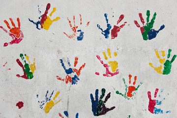 Peace concept - multi-colored kids hand prints on a white wall