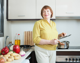 Smiling mature woman  in domestic kitchen