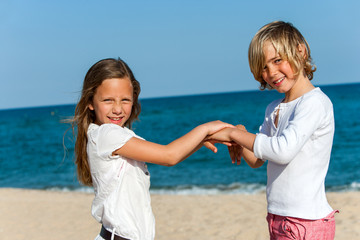 Two friends playing hand game on beach.