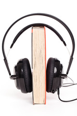Headphones and book on a white background