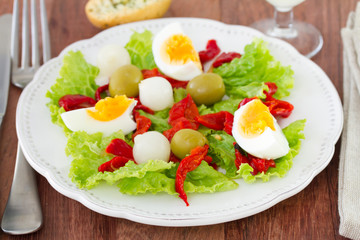 salad with egg and olive on the white plate