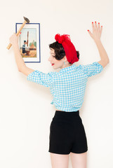 Funny pinup woman holding hammer and picture