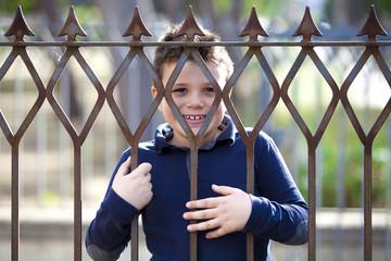 Bambino sorridente dietro le sbarre