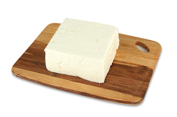 Sheep milk cheese on cutting board, isolated on white
