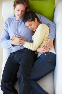 Overhead View Of Couple Relaxing On Sofa