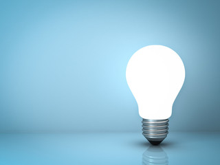 Light bulb standing on blue background with reflection