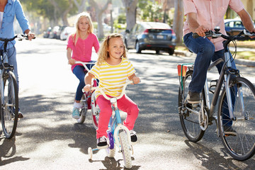 Family Cycling On Suburban Street