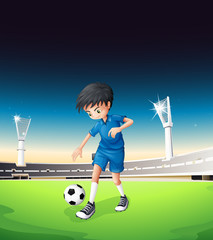 A soccer field with a boy playing