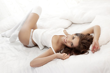 Cheerful attractive girl posing in white lingerie at the morning