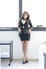 Young pretty business woman posing on office background