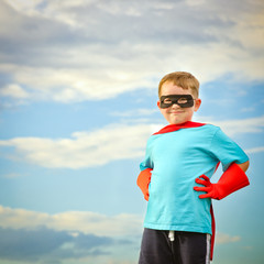 Child pretending to be a superhero with copy space