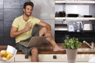 Handsome man with laptop in kitchen