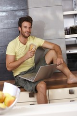 Happy man browsing internet in kitchen