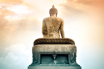 Back of big image of Buddha in Thailand with and cloud
