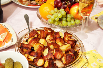 baked potatoes in bacon and other food dishes