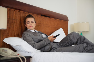 Concerned business woman laying on bed in hotel room