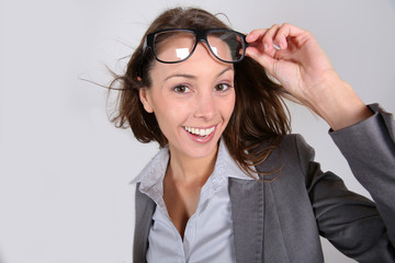 Funny businesswoman lifting eyeglasses up