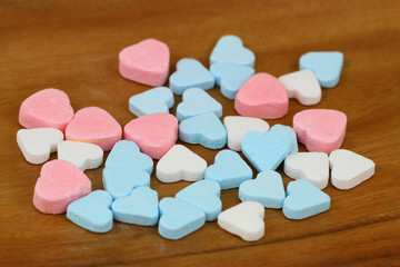 Colorful sugar hearts on wooden surface