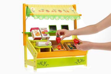 enfant jouant avec magasin jouet en bois