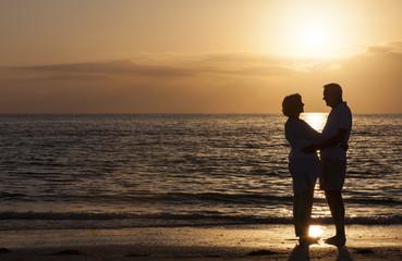 Happy Senior Couple Embracing on Sunset Beach
