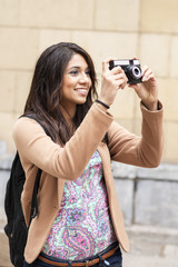 Young smiling woman taking pictures by city.