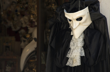 Mask with costume hanging in a shop in Venezia
