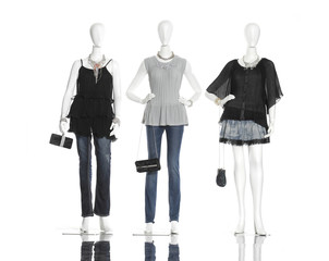 clothes in jeans, jewelry, black bag on three mannequin