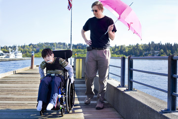 Father walking with disabled son out on lake pier
