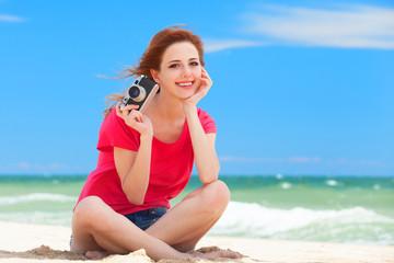 Redhead teen girl with retro camera on the beach
