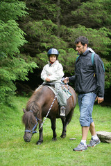 Father helping his daughter ride a pony