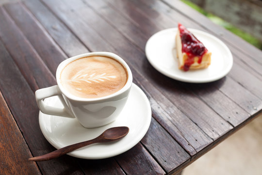 Cup of latte coffee with strawberry cheesecake