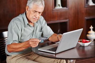 Senior bezahlt mit Kreditkarte im Internet