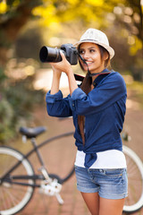 young woman taking pictures at the park