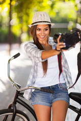 young woman taking self portrait outdoors