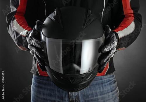 Wall mural Motorcyclist with helmet in his hands. Dark background