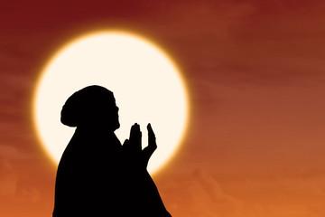 Silhouette of female muslim pray at sunset