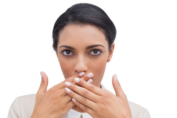 Shocked businesswoman putting her hand in front of her mouth