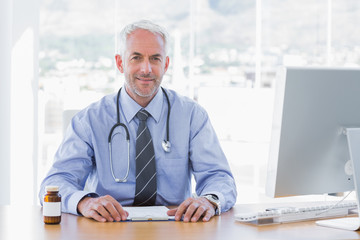 Attractive doctor sitting at his desk