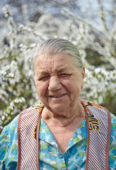 Smiling elderly woman in working clothes against a blossoming ga