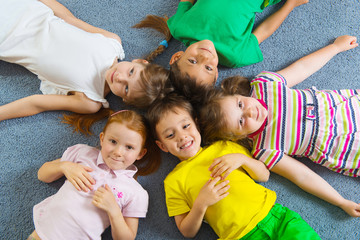 Cute little children lying on floor