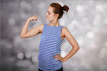 Funny girl in  vest shows off biceps at light background