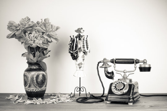 Vintage telephone and flowers on table sepia photo