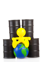 toy  little man sits next on butts to oil the globe.