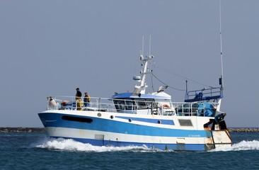 chalutier bleu et blanc navigant en mer