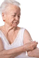 Old woman  giving herself an injection of insulin
