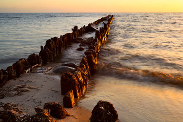 Wall Mural - old breakwater in North sea at sunset