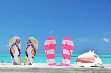 Two pairs of flip-flops against ocean. Exuma, Bahamas