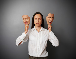 woman holding two masks with different mood