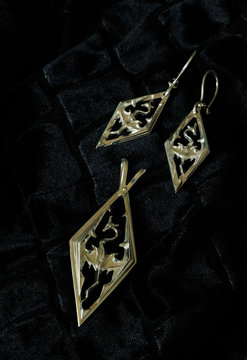 silver earrings and pendent with the image of a dragon on black