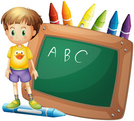 A boy beside a board with crayons at the back